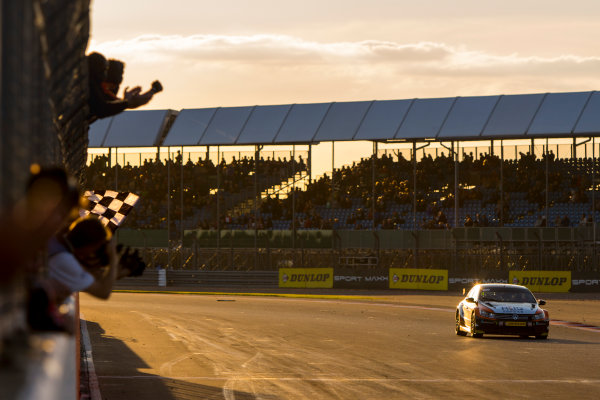 2015 British Touring Car Championship, Silverstone, Northamptonshire, England. 26th - 27th September 2015. Colin Turkington (GBR) Team BMR Volkswagen Passat CC, takes the chequered flag to win the race, as his team celebrate from the pit wall. World Copyright: Zak Mauger/LAT Photographic. ref: Digital Image _L0U4661