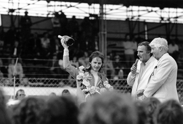 1977 British Grand Prix. Silverstone, England.14-16 July 1977. Gilles Villeneuve (McLaren M23 Ford) 11th position on his Grand Prix debut. Here with a bottle of champagne for being voted Driver of the Day, portrait. World Copyright: LAT Photographic. ref: 10208/21