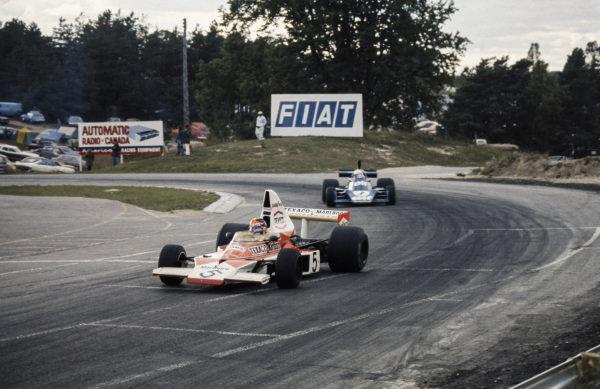 Emerson Fittipaldi, McLaren M23 Ford leads Jody Scheckter, Tyrrell 007 Ford.