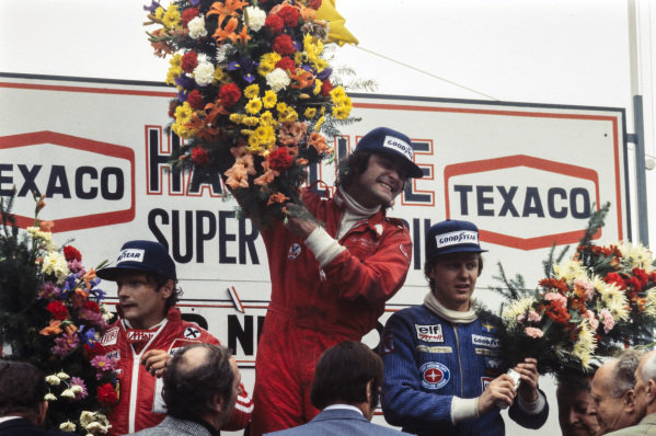 Gunnar Nilsson celebrates victory on the podium with Niki Lauda, 2nd position, and Ronnie Peterson, 3rd position.