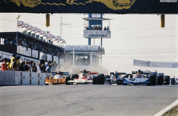 James Hunt, McLaren M23 Ford, leads the field at the start with Ronnie Peterson, March 761 Ford, alongside and Vittorio Brambilla, March 761 Ford coming up on the left.