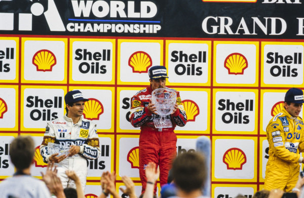 Nigel Mansell, 1st position, kisses his trophy on the podium. He is alongside Nelson Piquet, 2nd position, and Ayrton Senna, 3rd position.