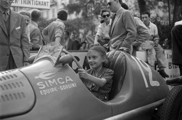 A young fan sits in the cockpit of Jean-Pierre Wimille's Simca-Gordini T11.
