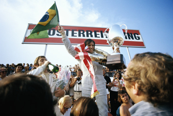 Emerson Fittipaldi celebrates victory on the podium with third place Peter Revson.