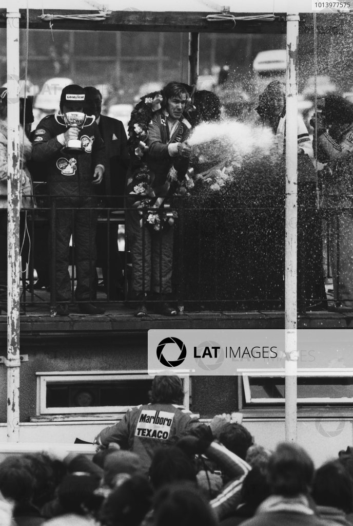 Brands Hatch, England. 14th March 1976. James Hunt (McLaren M23 Ford), 1st position, on the podium with Alan Jones (Surtees TS19 Ford), 2nd position and Jacky Ickx (Hesketh 308C Ford), 3rd position, portrait.  World Copyright: LAT Photographic. Ref: B/W Print.