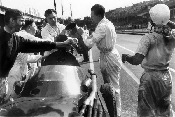 Aintree, England. 18-20 July 1957.Stirling Moss (Vanwall), 1st position, with Tony Brooks (extreme left) who gave up his car for Moss to drive after his car retired, portrait.World Copyright: LAT Photographic.Ref: 464 - 32.