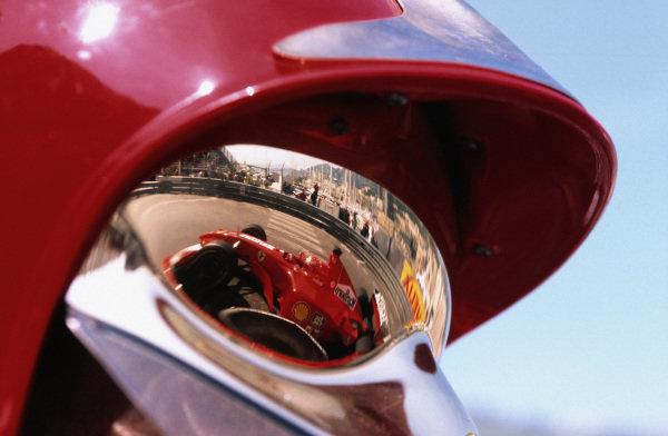 Michael Schumacher, Ferrari F2001, reflected in the visor of a fire marshal.