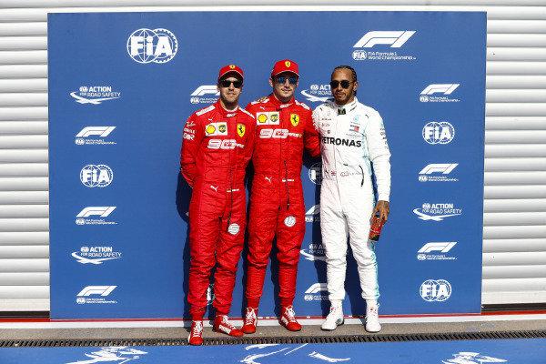 Charles Leclerc, Ferrari, celebrates pole position, with Sebastian Vettel, Ferrari, and Lewis Hamilton, Mercedes AMG F1