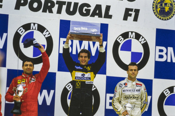 Ayrton Senna, 1st position, Michele Alboreto, 2nd position, and Patrick Tambay, 3rd position, stood on the podium with their respective trophies.