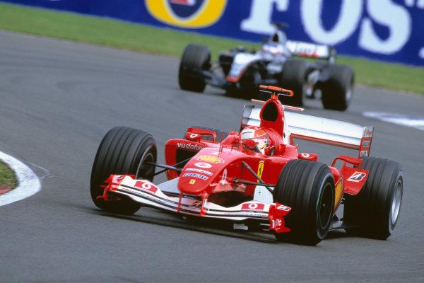 2004 British Grand PrixSilverstone England. 9th - 11th July.Michael Schumacher, Ferrari F2004 leads Kimi Raikkonen, McLaren Mercedes MP4/19. Action. World Copyright:Glenn Dunbar/LAT PhotographicRef:35mm image A08
