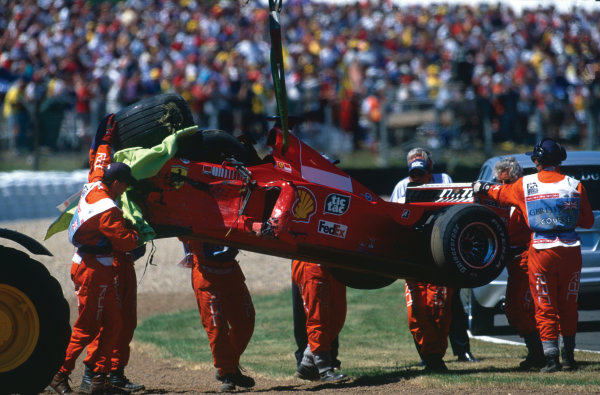 1999 British Grand Prix. Silverstone, England. 9th - 11th July 1999. Marshals remove the wrecked Ferrari F399 after Michael Schumacher had crashed heavily into the tyre barriers at Stowe on the first lap, breaking his leg. World Copyright: LAT Photographic.  Ref:  99_GB_MS_Crash_10.