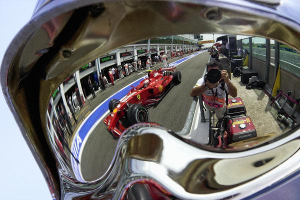 Kimi Räikkönen, Ferrari F2007 reflected in the safety helmet of the pit crew.