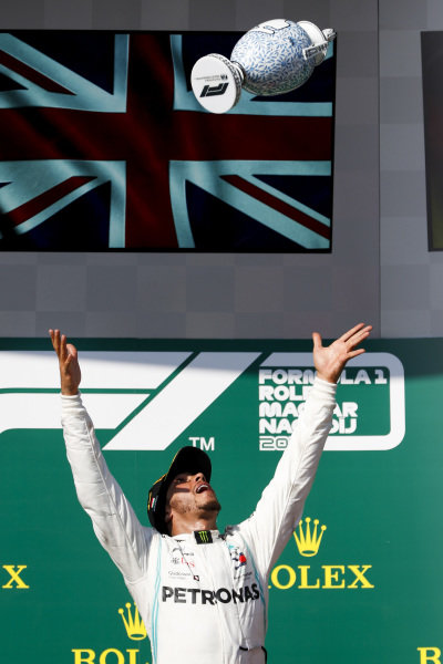 Lewis Hamilton, Mercedes AMG F1, 1st position, throws his trophy in the air in celebration on the podium