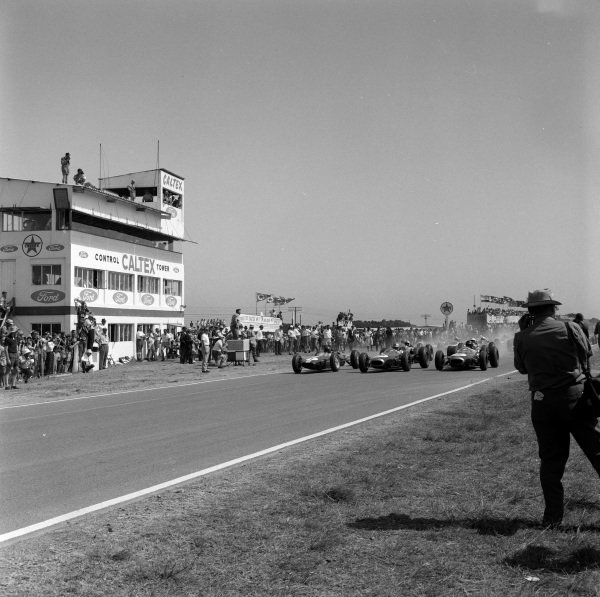 The start of the race, with Jim Clark, Lotus 25 Climax, Jack Brabham, Brabham BT7 Climax, and Dan Gurney, Brabham BT7 Climax, battling off the line.