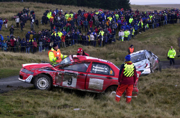 2002 World Rally Championship.Network Q Rally of Great Britain, Cardiff. November 14-17. Jani Paasonen's battered Lancer lies just off the road in front of Gronholm's similarly placed 206 WRC on Stage 10, Halfway 1.Photo: Ralph Hardwick/LAT