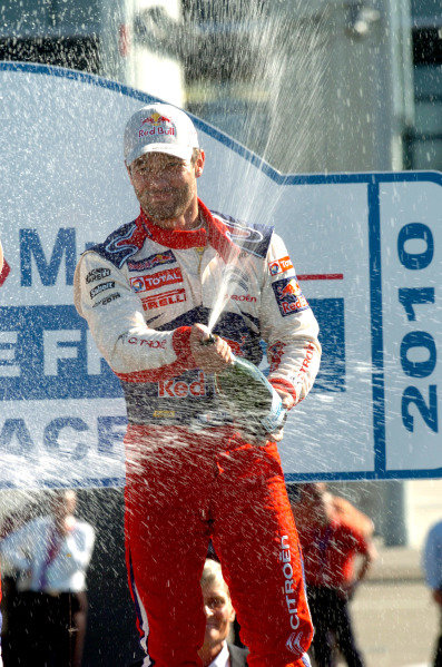 Sebastien Loeb (FRA), Citroen, sprays the winner's champagne (cremant d'Alsace) on the podium in Strasbourg as he celebrates his seventh world title.