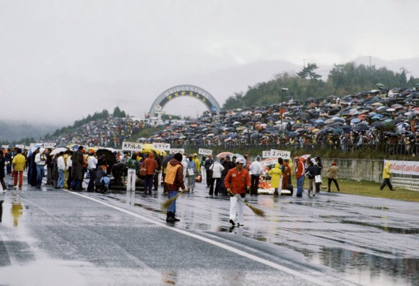 Two track officials at the front of the grid use brushes in a desperate attempt to sweep some of the surface water from the track surface. The inaugural Japanese GP was nearly cancelled before being run at the last possible moment in terrible conditions. Japanese Grand Prix, Rd 16, Fuji, Japan, 24 October 1976. BEST IMAGE