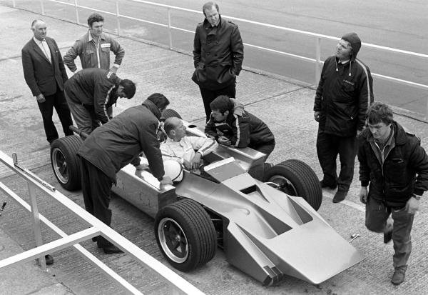 The Cosworth 4 wheel drive F1 car, here being driven by Mike Costin talking to designer Robin Herd, crouched next to car Silverstone 1969