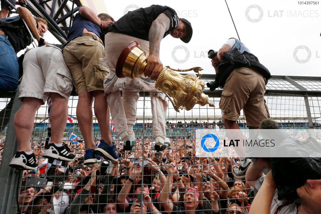 Silverstone Circuit, Northamptonshire, England. Sunday 5 July 2015. Lewis Hamilton, Mercedes AMG, 1st Position, shows his trophy to the crowds. World Copyright: Alastair Staley/LAT Photographic ref: Digital Image _79P4043