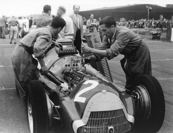 1951 British Grand Prix.Silverstone, Great Britain. 14 July 1951.Juan Manuel Fangio's Alfa Romeo 159 on the grid. Raymond Mays looks on in the background. Ref-4277B #4.World Copyright - LAT Photographic