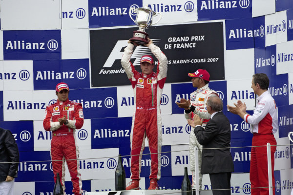 Kimi Raikkonen raises his winner's trophy on the podium as Felipe Massa, 2nd position, and Lewis Hamilton, 3rd position, applaud.