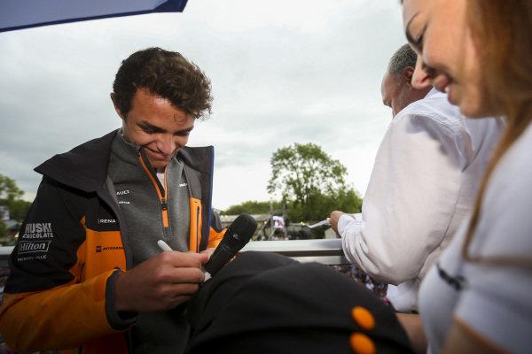 Lando Norris, McLaren signs hats for fans