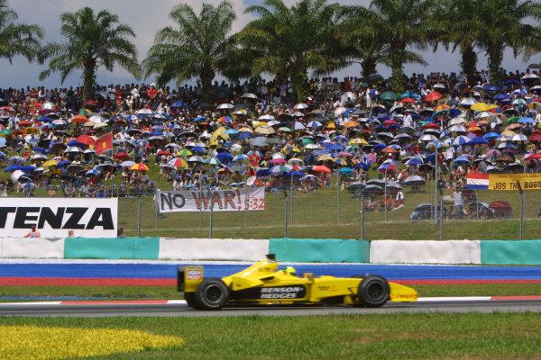 "2003 Malaysian Grand Prix. Sepang, Kuala Lumpur, Malaysia.21-23 March 2003.Ralph Firman (Jordan EJ13 Ford) 10th position, passes a ""no war"" banner.World Copyright - LAT Photographic ref: Digital Image Only"