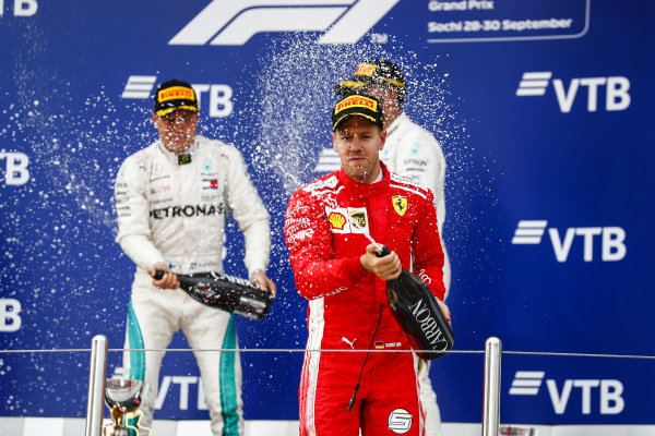 Valtteri Bottas, Mercedes AMG F1, 2nd position, Lewis Hamilton, Mercedes AMG F1, 1st position, and Sebastian Vettel, Ferrari, 3rd position, spray Champagne on the podium