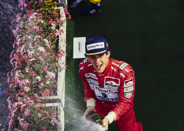 Ayrton Senna, 1st position, sprays champagne on the podium.
