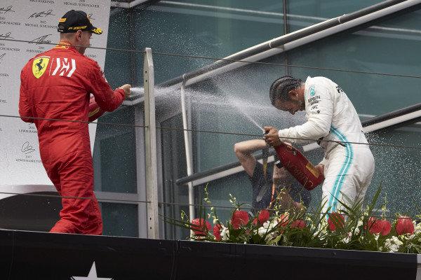 Sebastian Vettel, Ferrari, 3rd position, and Lewis Hamilton, Mercedes AMG F1, 1st position, celebrate on the podium with Champagne