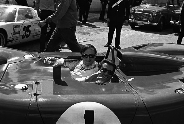 Monza, Itaty. 25th April 1969. Rd 4.Chris Amon gives team mate, Mario Andretti a lift through the paddock in their Ferrari 312P, retired, portrait. World Copyright: LAT Photographic.Ref:  B/WPRINT.