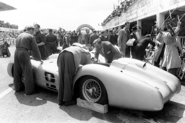 1954 French Grand Prix.Reims-Gueux, France. 4 July 1954.Mechanics work on the new streamlined Mercedes-Benz W196 in the pits. Juan Manuel Fangio and Karl Kling finished 1st and 2nd position respectively.World Copyright: LAT PhotographicRef: Black & print
