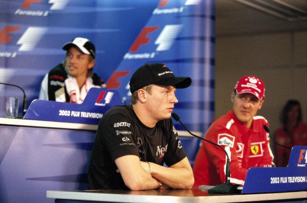 Kimi Räikkönen speaking in the press conference. Championship rival Michael Schumacher and Jenson Button are also present.
