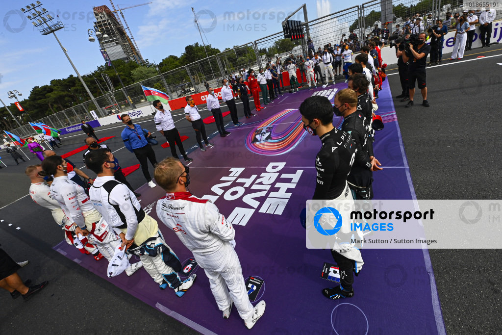 Team members and drivers stand for a minutes silence for the late Mansour Ojjeh prior to the start