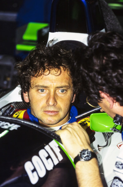Pierluigi Martini chats with a member of the team while he sits in his Minardi M195 Ford.