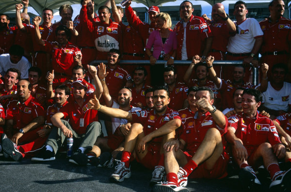 Sepang, Kuala Lumpur, Malaysia. 15-17 October 1999. Eddie Irvine (front) celebrates his 1st position with the Ferrari team and team mate Michael Schumacher (with wife Corinna). Ref: 99MAL04. World Copyright - LAT Photographic