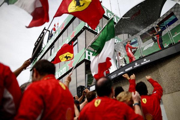 Sebastian Vettel, Ferrari, 1st position, and Max Verstappen, Red Bull Racing, 3rd position, spray Champagne on the podium.
