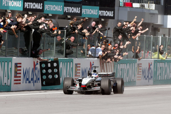 2003 Malaysian Grand Prix. Sepang, Kuala Lumpur, Malaysia.21-23 March 2003.Kimi Raikkonen (McLaren MP4/17D Mercedes) celebrates as he takes 1st position and his maiden Grand Prix win to the congratulations from the McLaren team.World Copyright - Steve Etherington/LAT Photographic ref: Digital Image Only