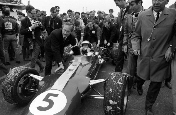 Colin Chapman and Keith Duckworth help push race winner Jim Clark, Lotus 49 Ford through the pit lane.