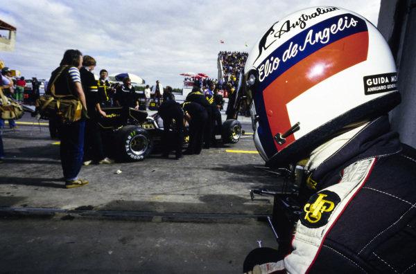 Elio de Angelis looks on as his mechanics work on his Lotus 95T Renault.