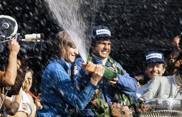 Carlos Reutemann celebrates victory on the podium with the champagne.