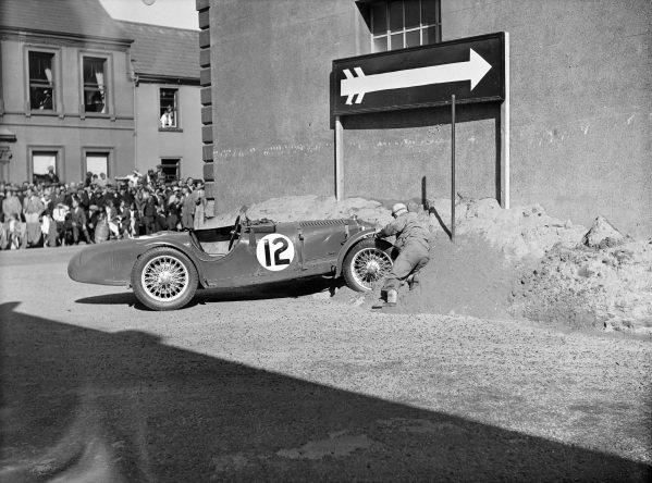 William van der Becke works to free his Riley TT Sprite from a sand bank.