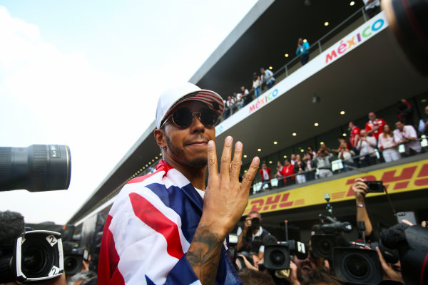 Autodromo Hermanos Rodriguez, Mexico City, Mexico. Sunday 29 October 2017. Lewis Hamilton, Mercedes AMG, with Union flag across his shoulders, holds four fingers up in celebration of becoming the first British 4 times world champion in history. World Copyright: Charles Coates/LAT Images  ref: Digital Image DJ5R7878