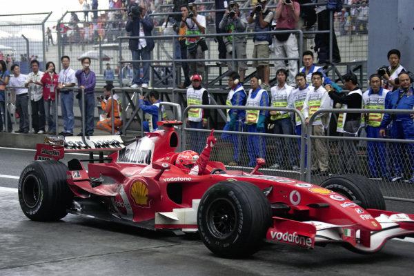 Michael Schumacher celebrating victory as he pulls his Ferrari 248 F1 into parc fermé.