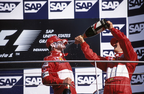 Rubens Barrichello and Ferrari team-mate Michael Schumacher spray champagne on the podium.