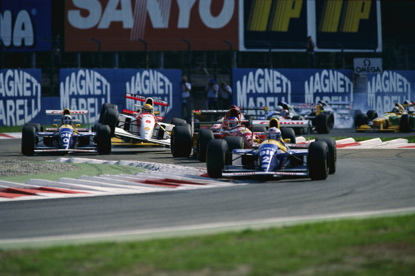 Alain Prost, Williams FW15C Renault, leads from Jean Alesi, Ferrari F93A, as Ayrton Senna, McLaren MP4-8 Ford, and Damon Hill, Williams FW15C Renault, collide at the start.