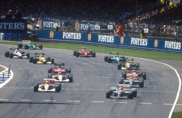 1991 British Grand Prix.Silverstone, England.12-14 July 1991.Nigel Mansell (Williams FW14 Renault) smokes the rears as he leads the grid away from Woodcote at the start, with Ayrton Senna (McLaren MP4/6 Honda), Riccardo Patrese (Williams FW14 Renault), Gerhard Berger (McLaren MP4/6 Honda), Alain Prost, Jean Alesi (both Ferrari 643's), Roberto Moreno, Nelson Piquet (both Benetton B191 Ford's) Mauricio Gugelmin (Leyton House CG911 Ilmor), Stefano Modena (Tyrrell 020 Honda), J J. Lehto (Dallara 191 Judd) and Andrea de Cesaris (Jordan 191 Ford) following behind. Ref-91 GB 13.World Copyright - LAT Photographic