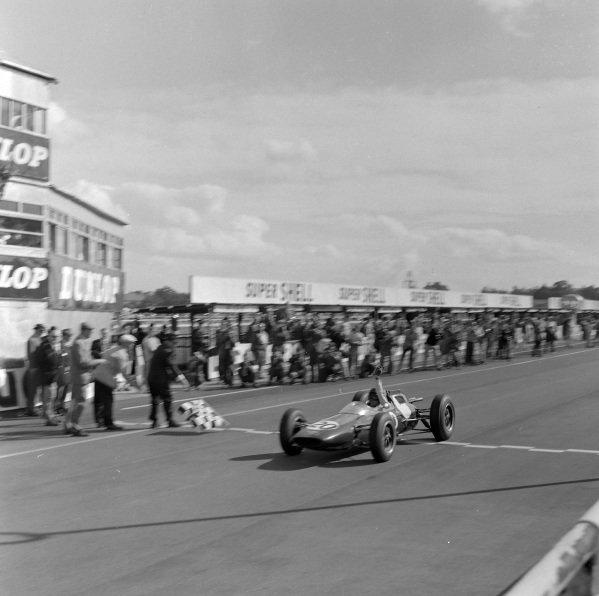 Jim Clark, Lotus 25 Climax, raises his arm in triumph as he takes the chequered flag.