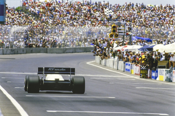 Keke Rosberg, Williams FW09 Honda, crosses the line at the finish, taking the chequered flag in the process.