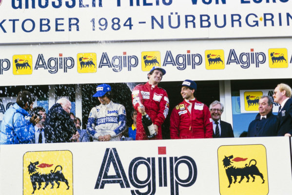 Alain Prost, 1st position, sprays champagne on the podium. Alongside are Michele Alboreto, 2nd position, and Nelson Piquet, 3rd position.